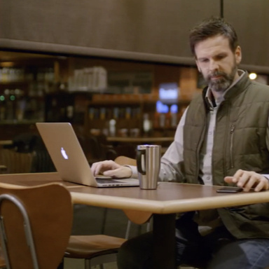 Man sitting at table with laptop, coffee, and smart phone