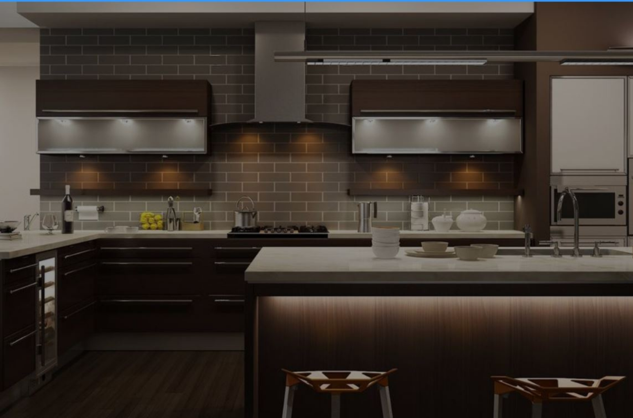 Residential kitchen with lighting in each appliance, white countertops, and gray backsplash