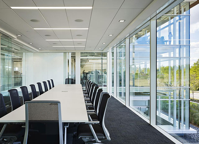 Conference room with white table, black chairs, and bright ambiance