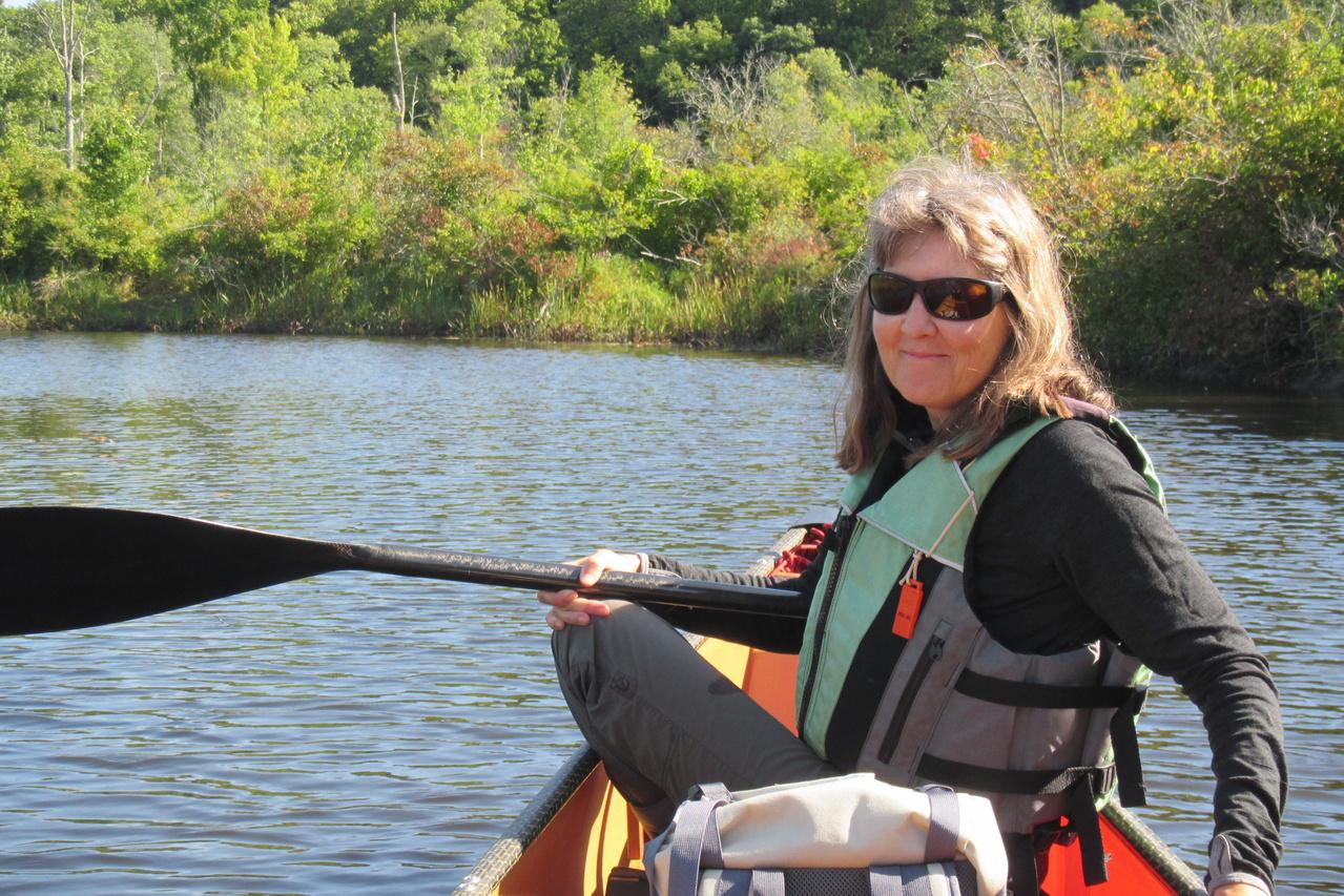 Renee Mercaldo-Allen canoeing on a river.