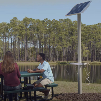 Man and woman at outdoor table next to solar charging station and pond