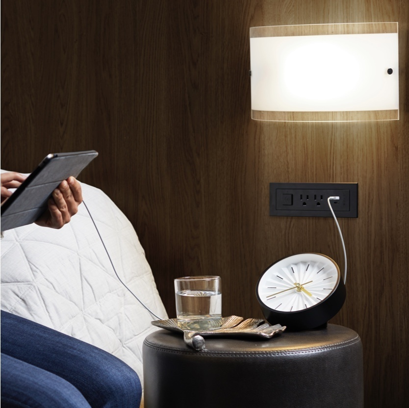 person sitting to the left holding a tablet that is plugged into a USB outlet strip built in to a wooden headboard above a side table with an analog clock and glass of water