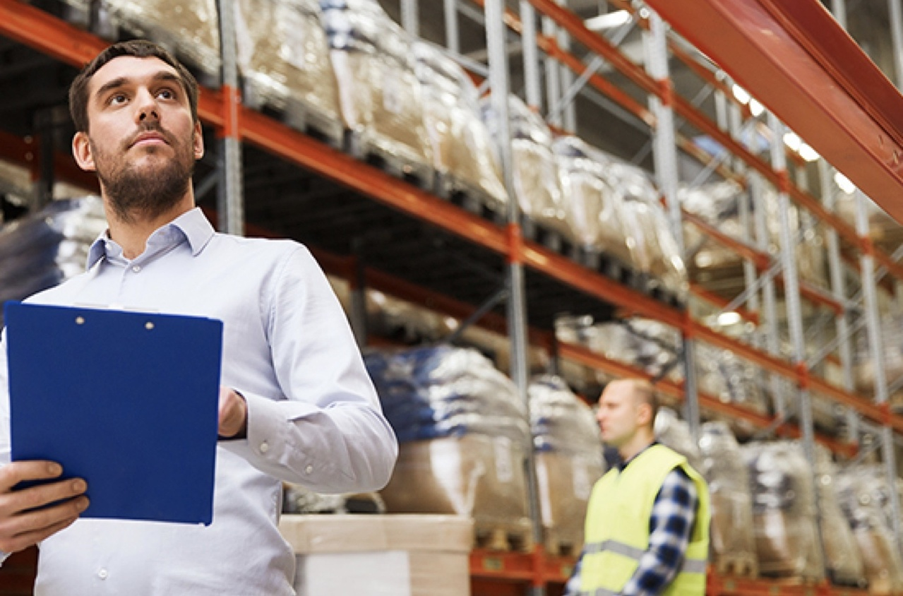 Man with clipboard in warehouse with worker in safety vest in background