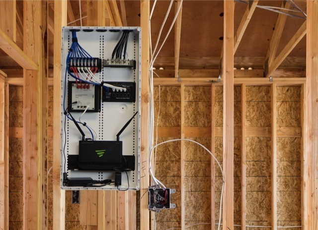 Back of electrical box with exposed wires in wooden frame of room