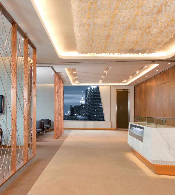 Lobby of a modern office building with taupe carpeting and a marble front desk