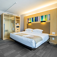 Modern light wood room with king bed and rainbow art