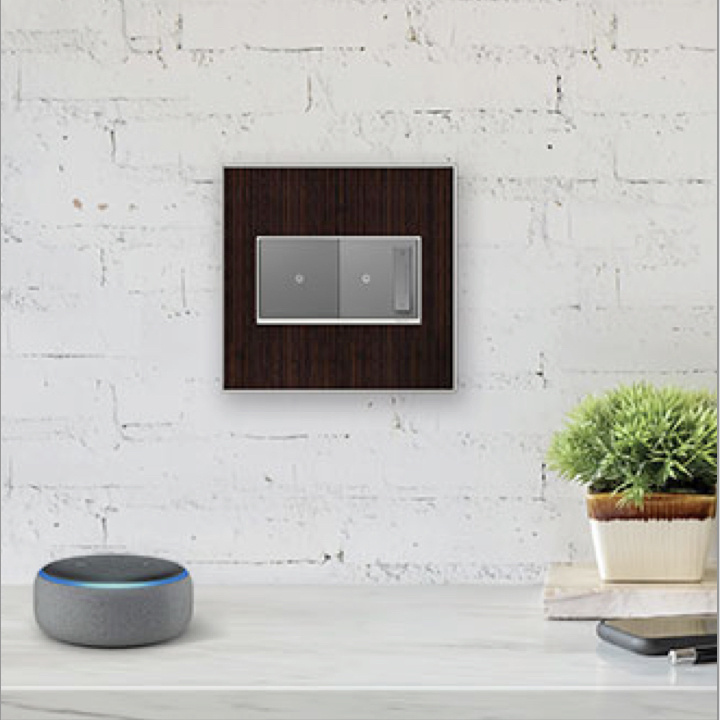 magnesium adorne Collection by Legrand switch and dimmer on white brick wall next to Amazon Alexa