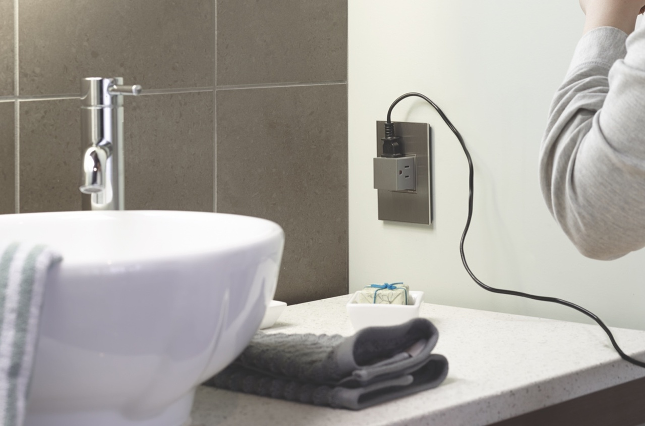 Legrand adorne Collection magnesium pop out outlet next to sink with cord plugged into it