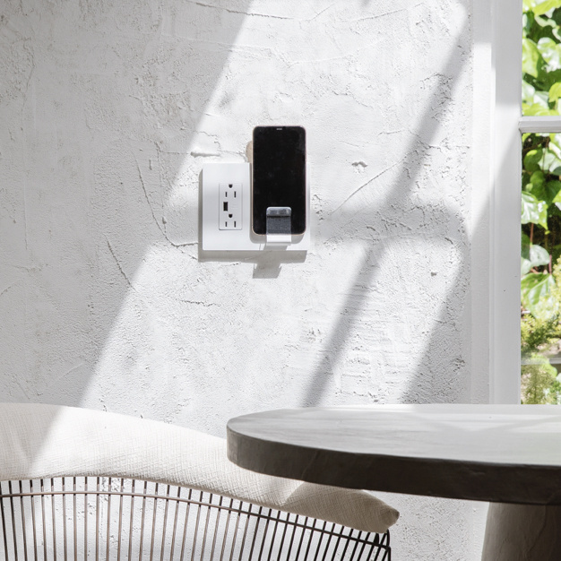 radiant Collection wireless charger in white charging a phone on an exterior wall next to sitting area