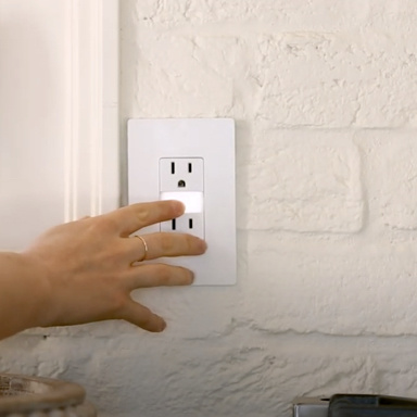 Hand touching nightlight in between white outlet on wall