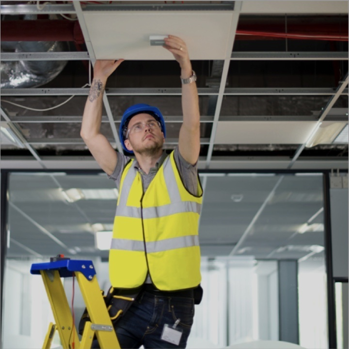 Man wearing contruction vest and goggles on a ladder installing a product into the ceiling