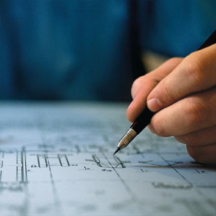 Hand holding pen over technical document
