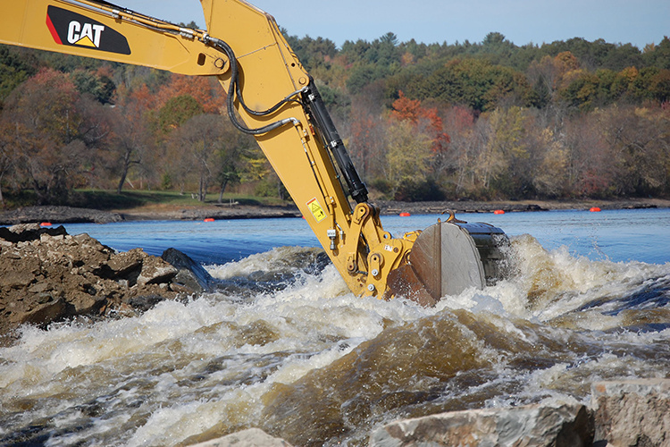 Heavy machinery removes dam debris from a river