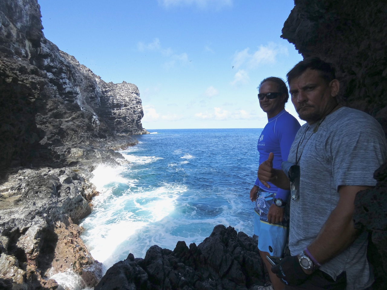 Rocky island and two men in front of the ocean.