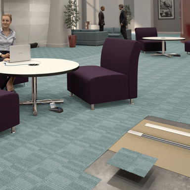 Commercial office space with Connectrac under-carpet raceway providing power to work table