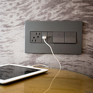 magnesium outlet and switches charging ipad on wood table
