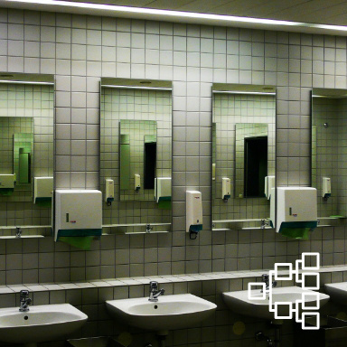 Three sets of public bathroom sinks mounted on a white tiled wall with mirrors and paper towel dispensers mounted above
