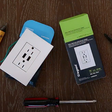 adorne Collection double USB outlet with white wall plate next to packaging and screwdriver on wooden table