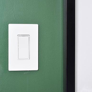 White switch on dark green wall
