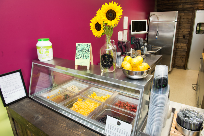 Sunflowers and fresh fruits and veggies greet Juice Bar customers.