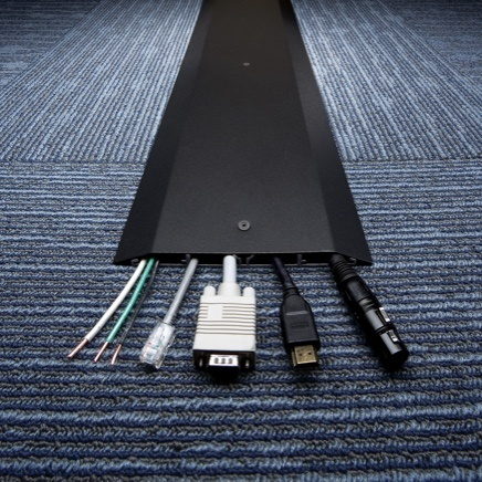 Black overfloor raceway installed on carpet with visible end power and AV connections