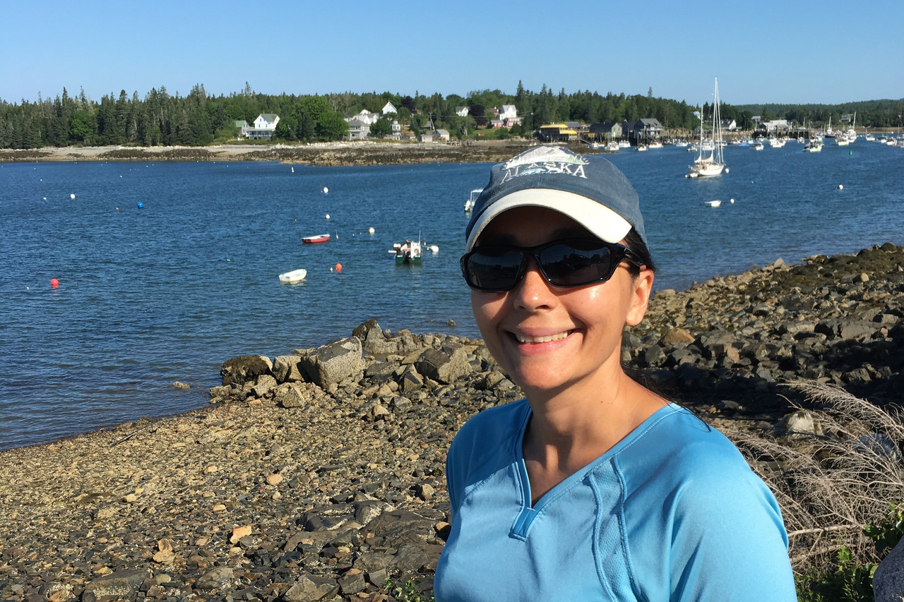 Elizabeth Methratta wearing a baseball hat and sunglasses standing by a harbor in Maine with small boats at moorings