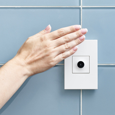 hand waving in front of wave light switch on blue tile