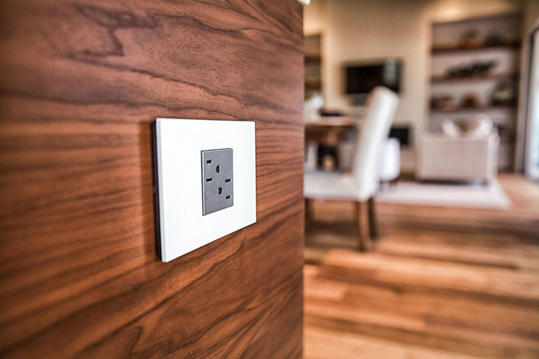 adorne white wall plate with tamper resistant outlet on wood wall
