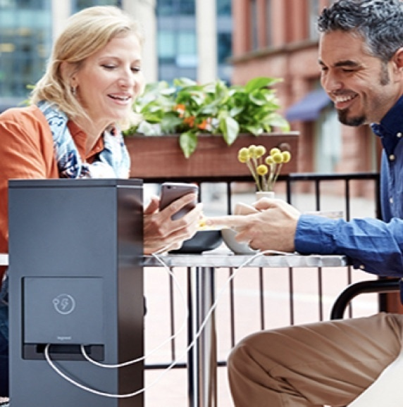 Man and woman charging their phone at an outdoor charging station