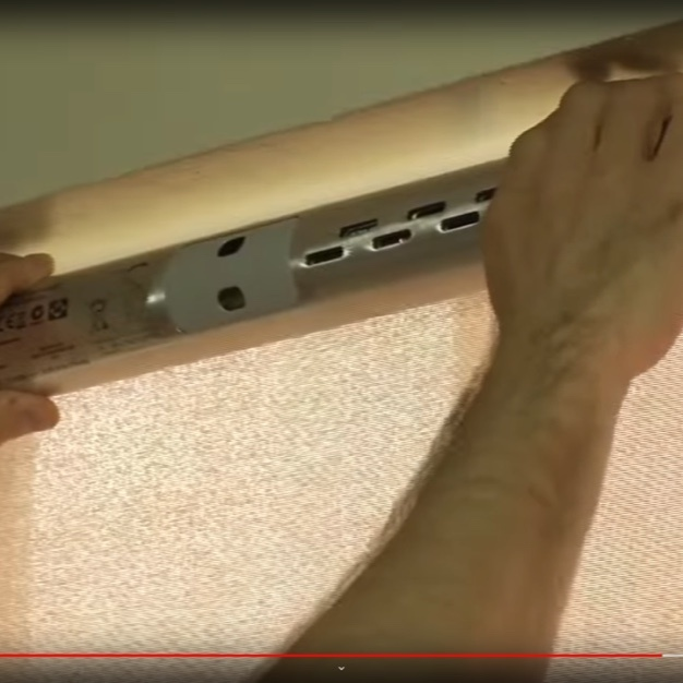 Person installing automatic roller shade mechanism