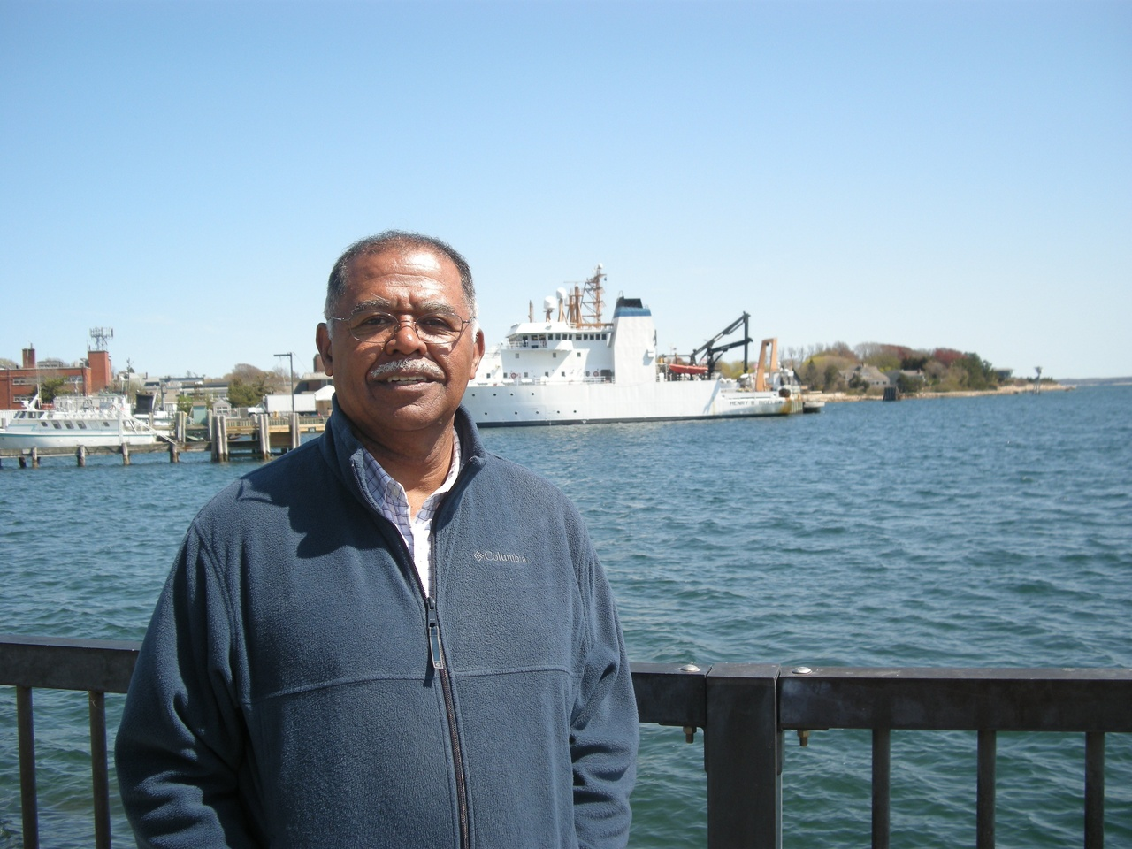 Ambrose Jearld Jr. stands by the water with the NOAA Ship Henry Bigelow in the background