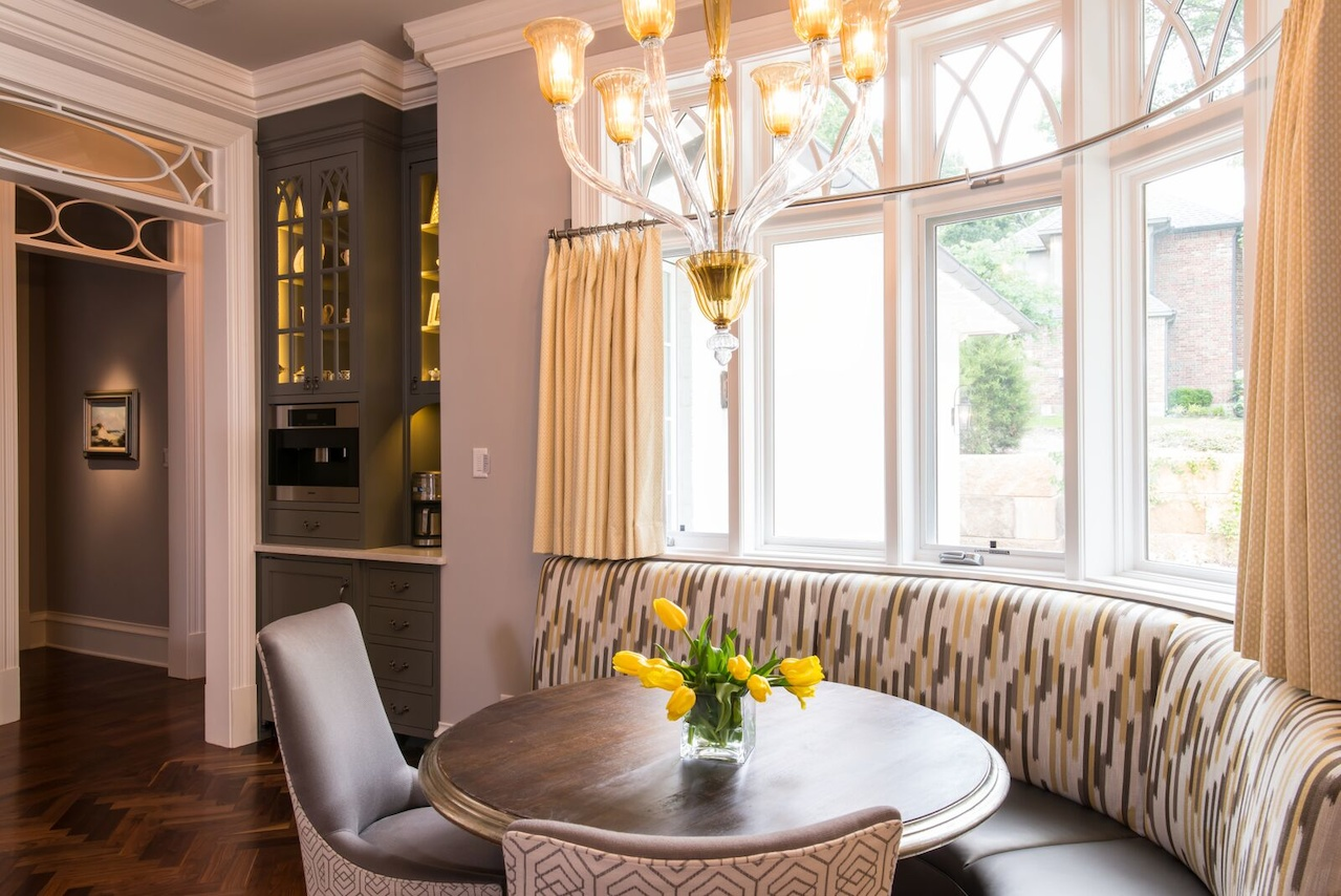 Mitchell Gold chairs with a lively fabric on the back add to the charm at the curvy seating area. A built-in Miele coffee machine is nearby.