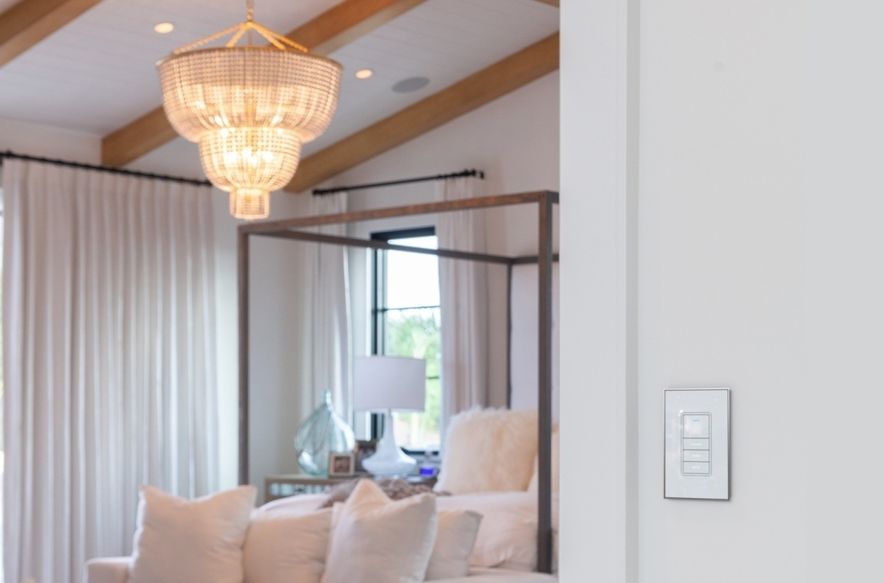 White lighting keypad on wall with luxurious bedroom in background