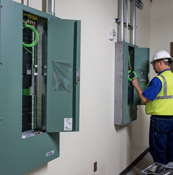 Electrician checking a circuit breaker box in a commercial office
