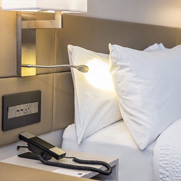 adorne furniture power center in upholstered headboard next to hotel bed
