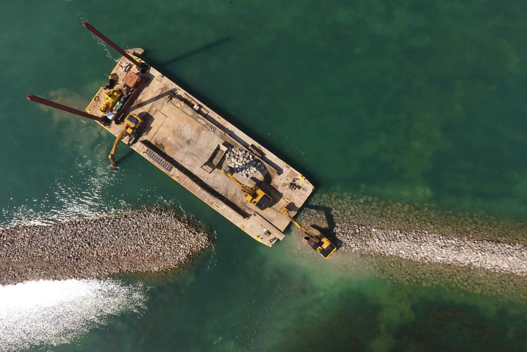 A barge and heavy equipment build offshore shoals on Celeron Island.