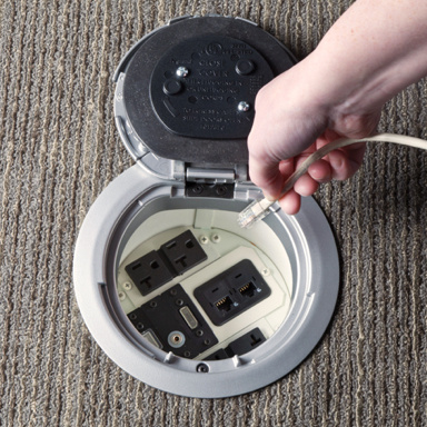 Evolution poke-thru device open in carpet surface with hand reaching to plug in cord