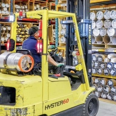 Man driving a forklift in a manufacturing warehouse