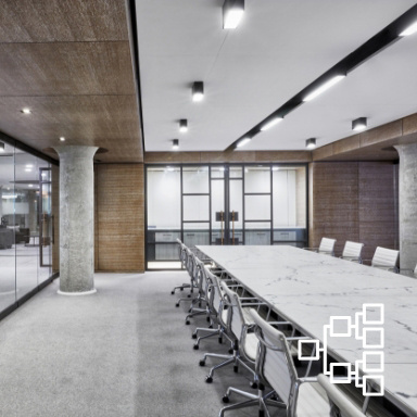 Very large conference room with marble floors and large cement pillars containing a long marble conference table with a dozen rolling chairs around it
