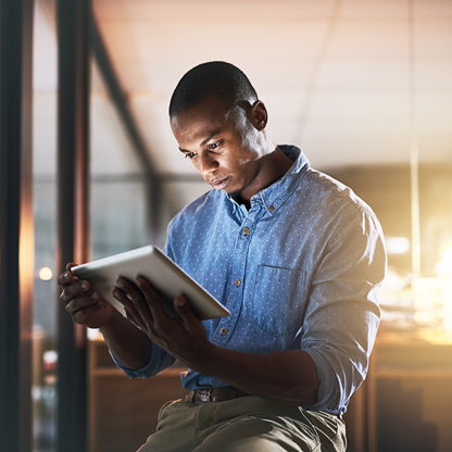 Man using tablet with back lighting producing a glow