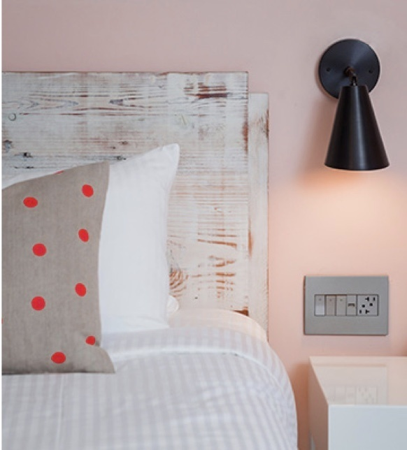 adorne furniture power center on pink wall above hotel nightstand
