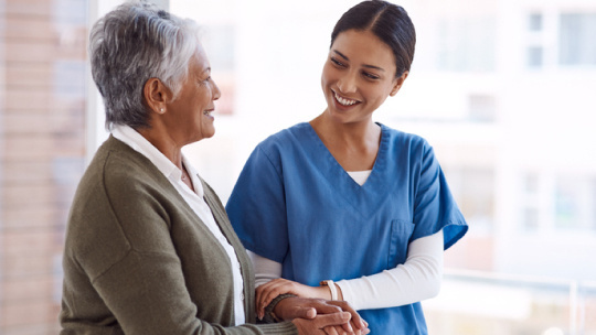 Nurse and patient holding hands and smiling