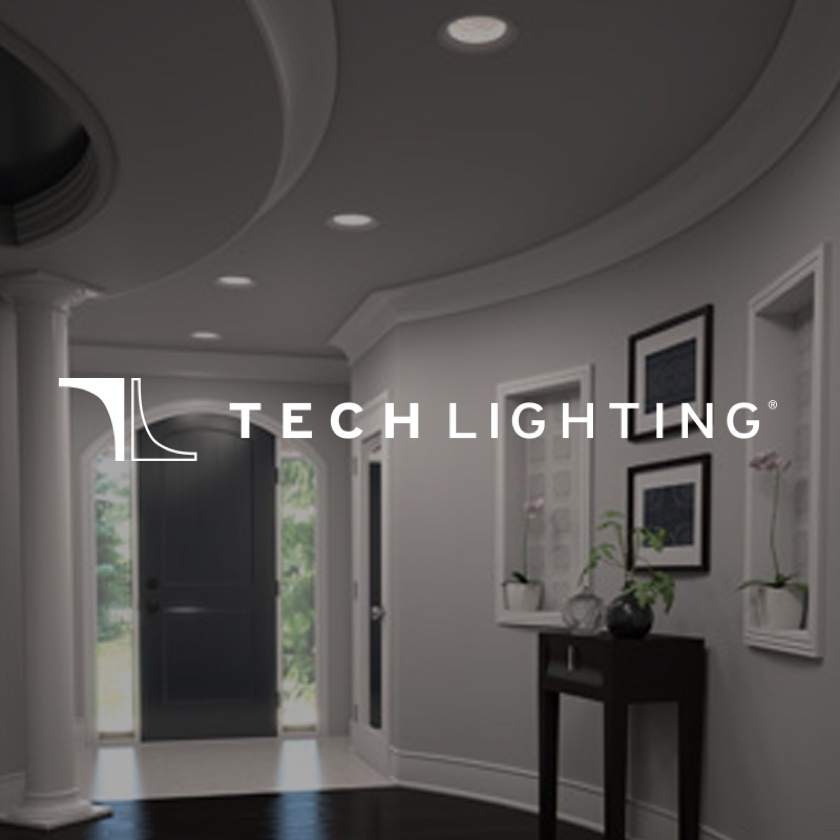 Gray foyer with black door and lights on with Tech Lighting logo in the foreground