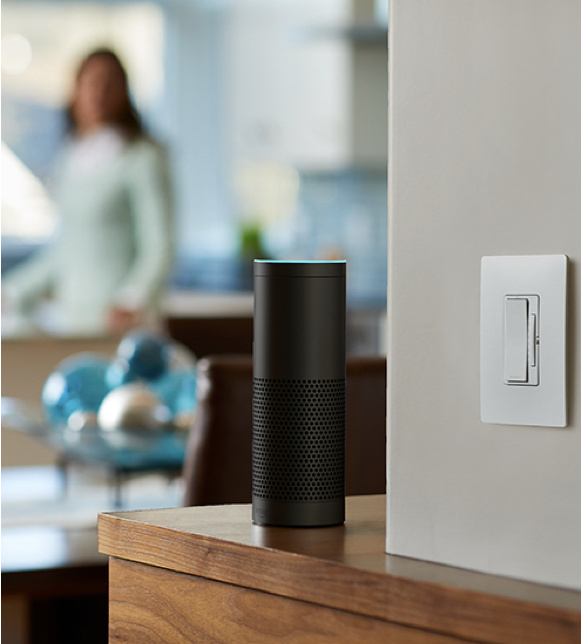 Amazon Alexa next to a smart dimmer light switch on beige wall with blurred woman in the background