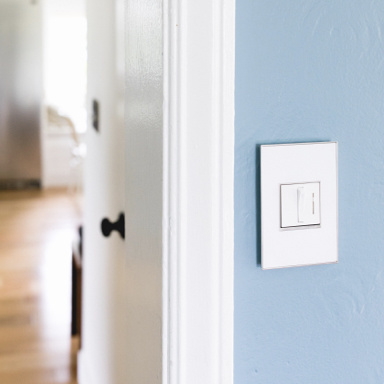 white wall plate and switch against light blue wall by door