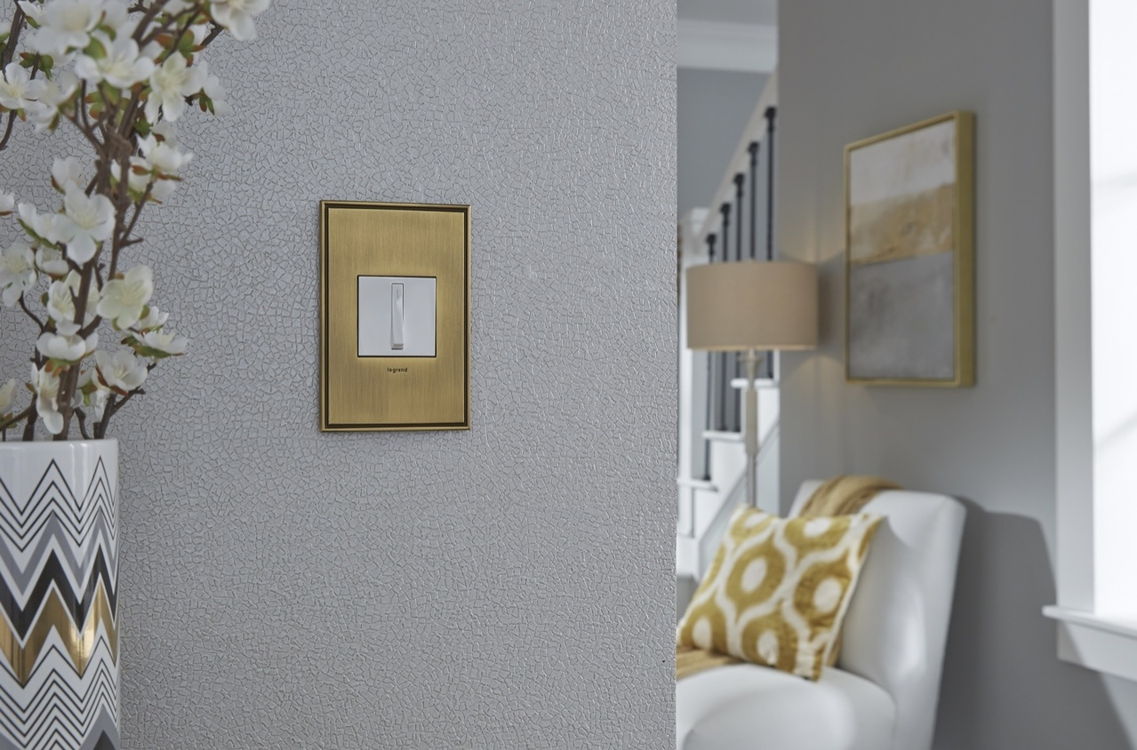 adorne white whisper switch with gold wall plate against gray hallway wall