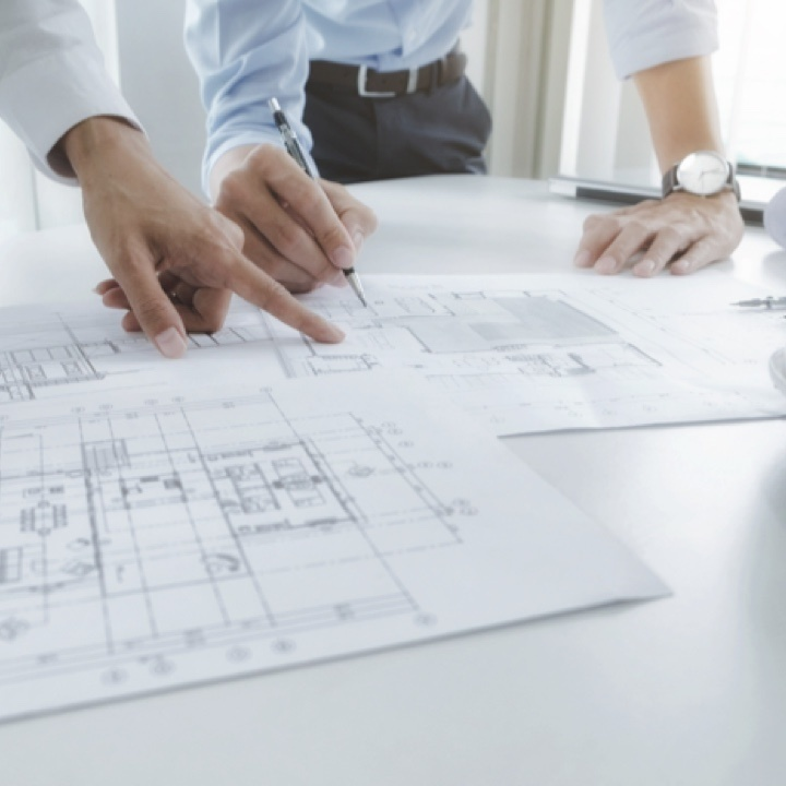 People pointing to engineering designs laid out on a table