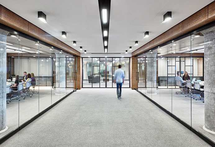 Commercial office hallway with glass-walled conference rooms on each side