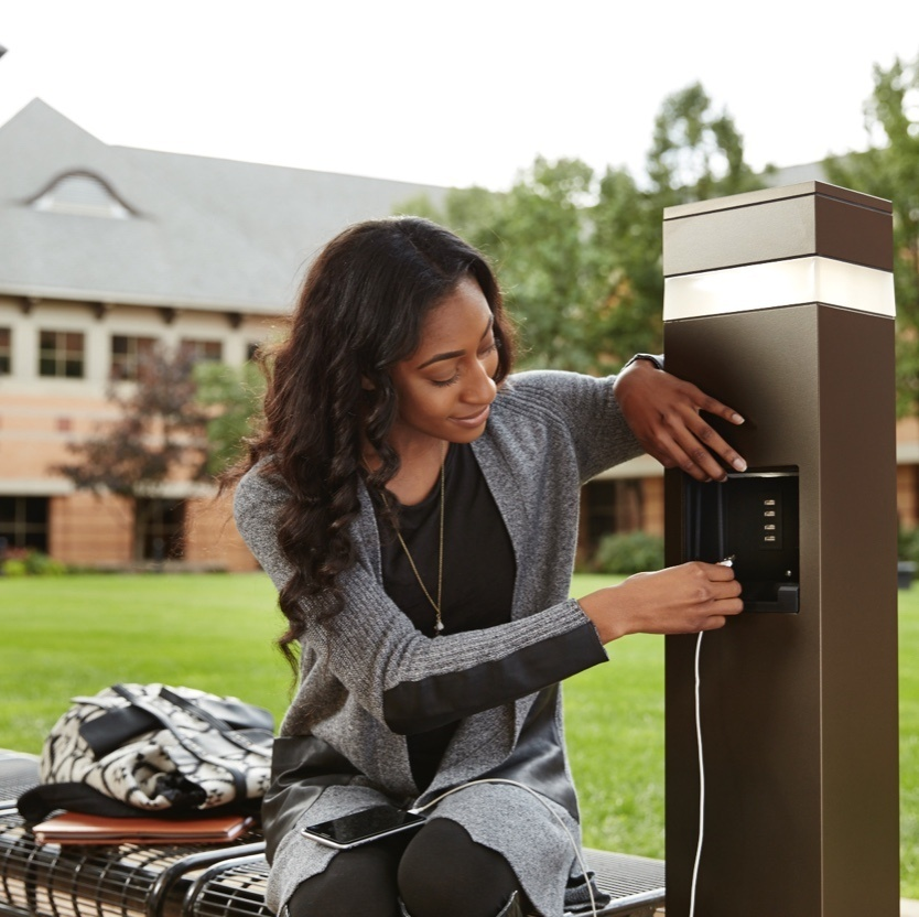 Image of a woman using an Outdoor Charging Station to charge her device