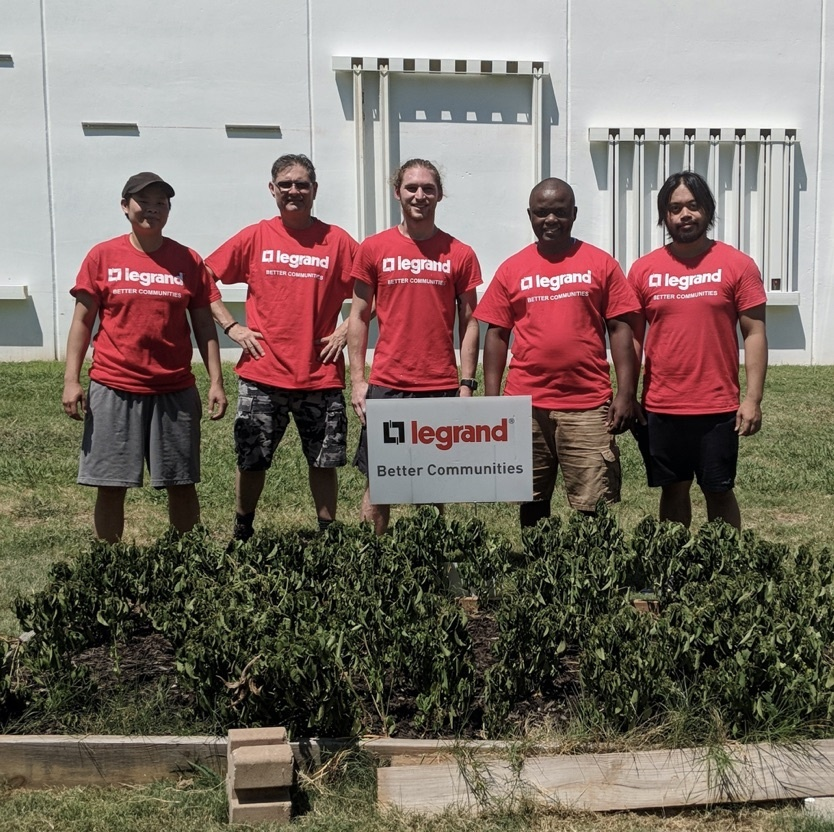 Legrand employees in red shirts in front of a Better Communities sign